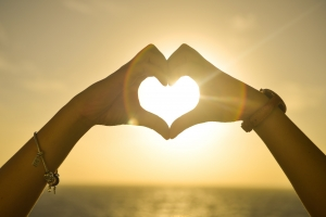 Hands making a heart with sunshine streaming through