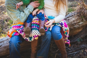 family picture of a small child siting on a colorful blanket on the parents lap