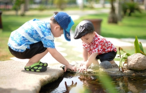 Two toddlers playing and reaching into a pond.