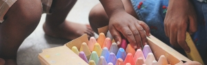 Kids getting chalk from a box full of different colored chalk crayons