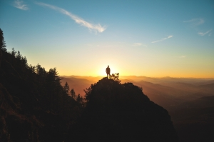 Person standing on a mountain top, facing the sunrise