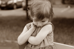 Sad toddler with crossed arms and looking down