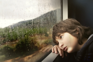 Boy looking sad and staring out a raining window
