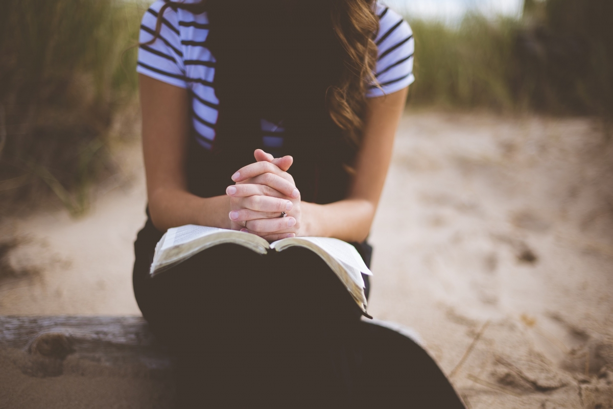 Woman praying outdoors with a bible in her lap, hands folded