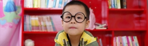 Kid with big round blag glasses looking at the camera and holding a book