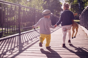 Two kids holding hands and walking across a bridge