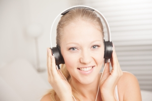 Woman listening to something through headphones that she is holding to her ears