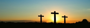 Three crosses silhouetted by a rising sun against a blue sky
