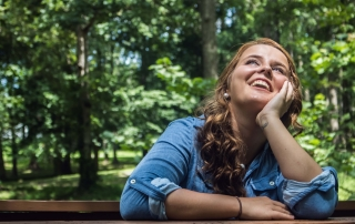 Woman sitting on a bench in the woods smiling and looking up