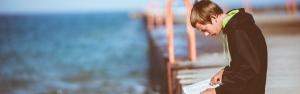 Teenage boy sitting on a dock reading