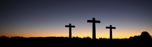 Three crosses silhouetted by the sunrise behind them